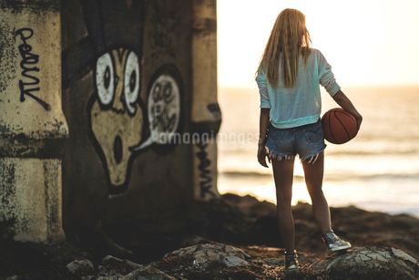 Young woman standing in front of a sunset holding a basketball.の写真素材 [FYI02259423]