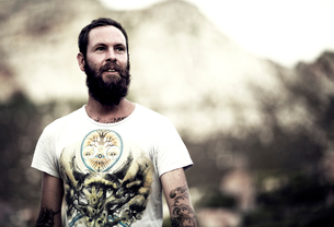 Portrait of bearded man wearing printed T-Shirt, tattoos on arms and chest, mountains in the backgroの写真素材 [FYI02259443]