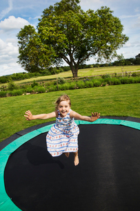Girl in a sundress jumping on a trampoline in a garden.の写真素材 [FYI02259452]