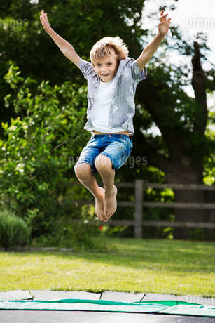 Boy wearing shirt and denim shorts jumping on a trampoline in a garden.の写真素材 [FYI02259457]