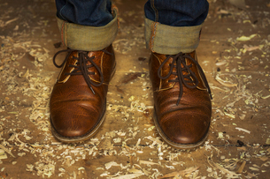 Feet and ankles of a man wearing denim jeans with turn up and traditional lace up brown leather shoeの写真素材 [FYI02259477]