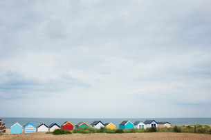 Row of colourful painted beach huts on a sandy beach under a cloudy sky.の写真素材 [FYI02259496]