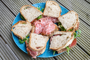 High angle close up of  selection of sandwiches with coppa and salami on a blue plate.の写真素材 [FYI02259500]