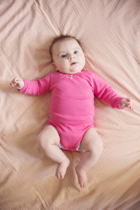 High angle view of baby girl wearing pink onesie lying on a bed.の写真素材 [FYI02259510]