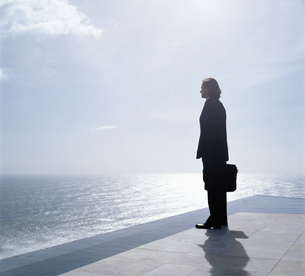 Businessman wearing dark suit holding briefcase, standing outdoors at edge of the ocean.の写真素材 [FYI02259514]