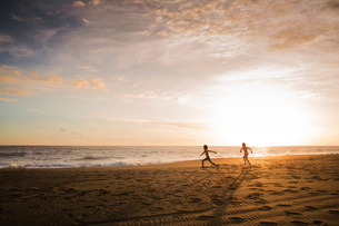 Two children running across the sand towards the sea, at sunset.の写真素材 [FYI02259522]