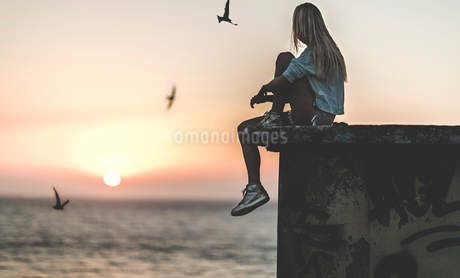 Side view of a young woman sitting on a wall with a sunset behind.の写真素材 [FYI02259539]