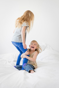 Two blond girls on a bed, younger girl sitting, holding on to legs of older girl standing.の写真素材 [FYI02259543]