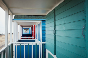 The terraces of a row of wooden painted beach huts on a beach in England.の写真素材 [FYI02259555]