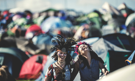 Two smiling young women at a summer music festival face painted, wearing feather headdress, standingの写真素材 [FYI02259557]