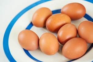 Close up high angle view of fresh brown eggs on a white plate with blue stripes.の写真素材 [FYI02259570]