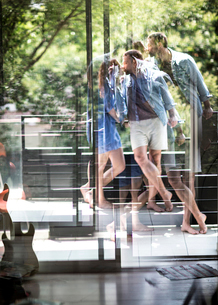 A couple standing on a balcony kissing, seen through a glass door.の写真素材 [FYI02259574]