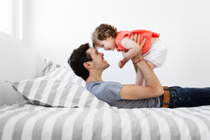 Man wearing grey T-shirt and jeans lying on bed with stripy duvet, playing with baby girl in red dreの写真素材 [FYI02259577]
