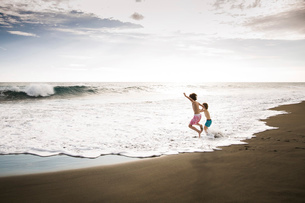 Two children, young boys playing at the water's edge on a sandy beach.の写真素材 [FYI02259581]