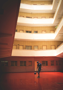 Young man playing with a ball in the internal courtyard of a building.の写真素材 [FYI02259589]