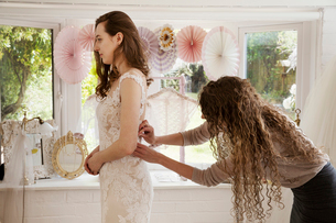 A dressmaker taking in a wedding dress, pinning and fitting it to the client, a young woman. A brideの写真素材 [FYI02259607]