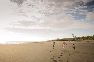 Three children running across the sand leaving three sets of footprints, on a beach.の写真素材 [FYI02259612]