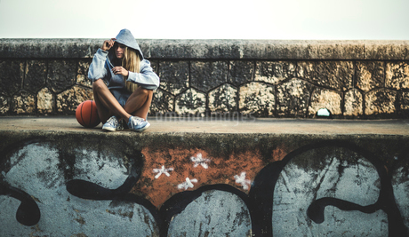 Young woman sitting on a wall holding a basketball.の写真素材 [FYI02259613]