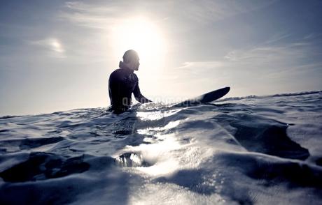 Surfer wearing wetsuit sitting on surfboard in the ocean.の写真素材 [FYI02259617]