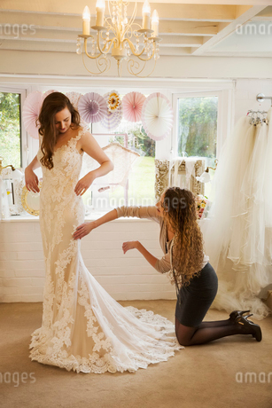 A dressmaker taking in a wedding dress, pinning and fitting it to the client, a young woman. A brideの写真素材 [FYI02259619]