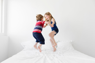 A six year old girl and four year old boy, brother and sister jumping up and down on a double bed.の写真素材 [FYI02259630]