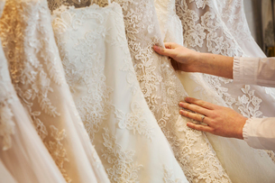 Rows of wedding dresses on display in a specialist wedding dress shop. Close up of full skirts, someの写真素材 [FYI02259636]