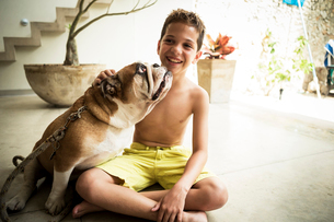A boy and a dog sitting on the floor together.の写真素材 [FYI02259642]