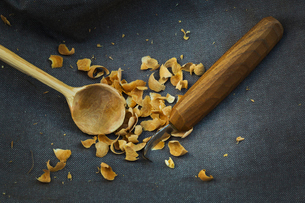 Close up of a handmade handcarved wooden spoon with round bowl end, a sharp carver's knife and woodの写真素材 [FYI02259644]