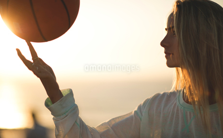 Young woman standing in front of a sunset spinning a basketball on her finger.の写真素材 [FYI02259646]