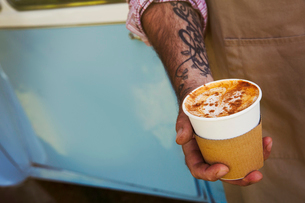 Close up of man with tattoo on his arm holding paper cup with cappuccino.の写真素材 [FYI02259649]