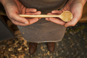 A man's hands holding a hand carved wooden spoon with a long tapering handle and smooth round bowl eの写真素材 [FYI02259661]