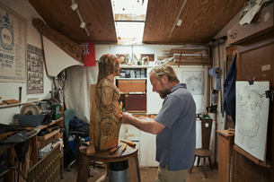 A wood carver standing in his workshop, using hand tools to shape and create decoration on a work inの写真素材 [FYI02259662]