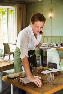 Woman wearing apron setting table in a restaurant.の写真素材 [FYI02259692]