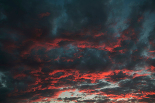 Black clouds in the sky, tinged orange and red by the setting sun.の写真素材 [FYI02259702]