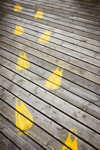 Yellow footprints on a traditional wooden pier in a coastal town.の写真素材 [FYI02259705]