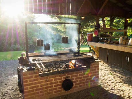 A brick built rustic woodburning barbecue grill lit in a garden.の写真素材 [FYI02259712]