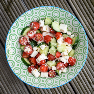 High angle close up of Greek Salad with tomato, cucumber and Feta cheese on a white and green plate.の写真素材 [FYI02259717]