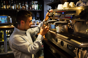 Side view of man standing at an espresso machine, frothing milk.の写真素材 [FYI02259727]
