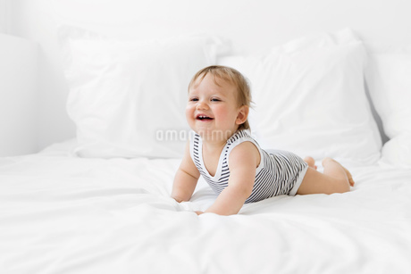 Baby boy wearing striped onesie lying on bed with white duvet.の写真素材 [FYI02259729]