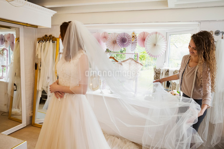 A young woman in a full length white wedding dress, and an assistant or dressmaker holding out her lの写真素材 [FYI02259730]