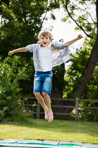 Boy wearing shirt and denim shorts jumping on a trampoline in a garden.の写真素材 [FYI02259739]