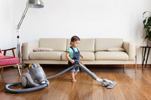 Young boy wearing denim dungarees, standing in front of sofa, hoovering hardwood floor.の写真素材 [FYI02259741]