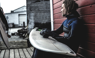 A surfer wearing a wetsuit sitting by a wooden building with a surfboard on his knees.の写真素材 [FYI02259744]