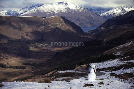 Mountain valley with snow-capped peaks and a lake in the distance, a snowman in the foreground.の写真素材 [FYI02259745]