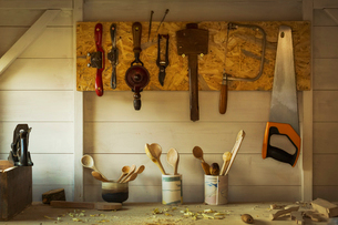 Ceramic pots with a selection of finished handmade wooden spoons and hand tools for carving and cuttの写真素材 [FYI02259755]