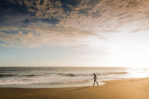 One person walking along the water's edge on a sandy beach at sunset.の写真素材 [FYI02259787]