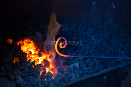 Close up of glowing metal rod with a scrolled end, held over hot coals in a blacksmith's workshop.の写真素材 [FYI02259798]