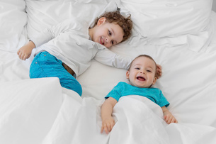 High angle view of boy wearing blue trousers and baby boy wearing blue T-shirt on a bed.の写真素材 [FYI02259806]