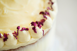 Close up high angle view of a cake decorated with cream and purple flower petals.の写真素材 [FYI02259809]