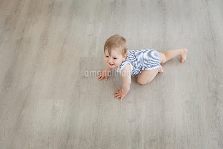 High angle view of baby boy wearing striped onesie crawling across hardwood floor.の写真素材 [FYI02259812]